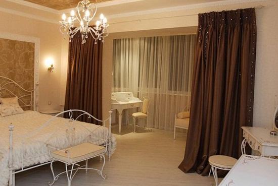 Зонирование пространства спальни при помощи коричневых штор