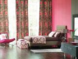 Серые с розовыми цветами шторы в спальне с однотонной отделкой