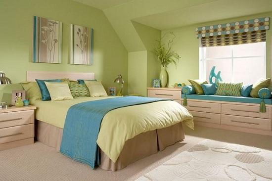 Просторная спальня со светлой мебелью и отделкой стен оливкового цвета