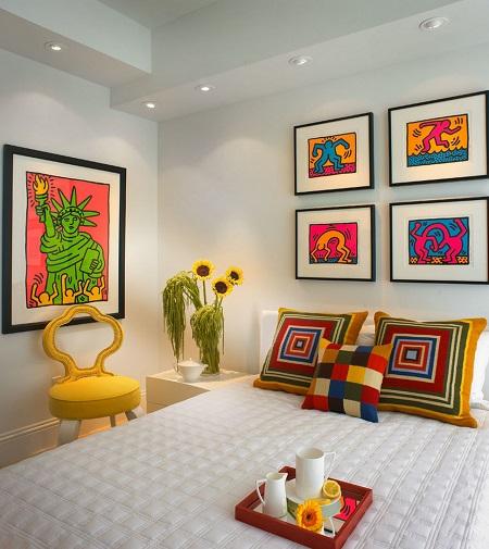 Идея декорирования белой спальни картинами и текстилем ярких красок