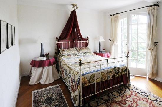 Яркий текстиль в спальне с белой отделкой стен