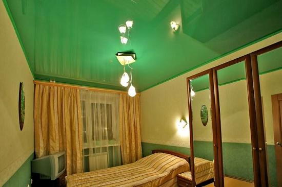Натяжной потолок интенсивного зеленого цвета в спальне