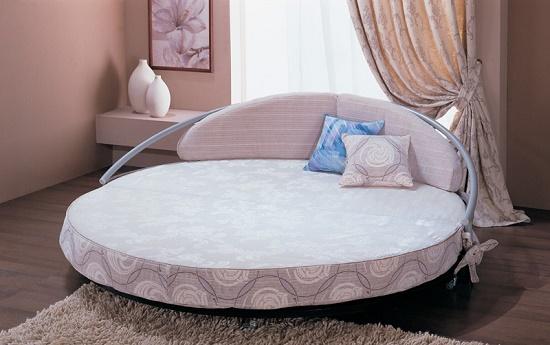 Кровать круглой формы на металлическом каркасе в спальне