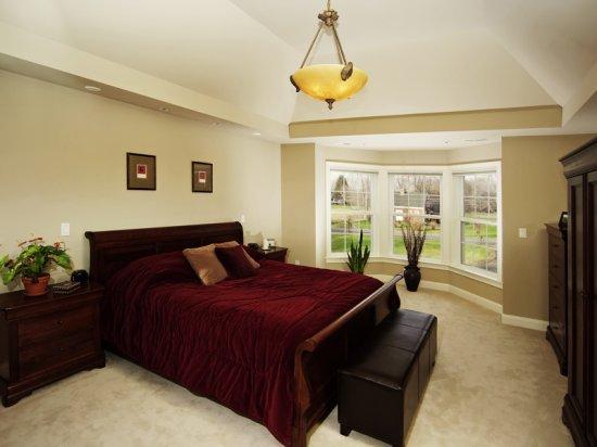 Потолочная люстра с матовым освещением в центре спальни