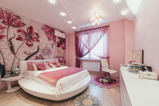 Розовая спальня с большими яркими цветами на стене