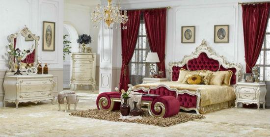 Просторная спальня с белой отделкой стен и красным текстилем