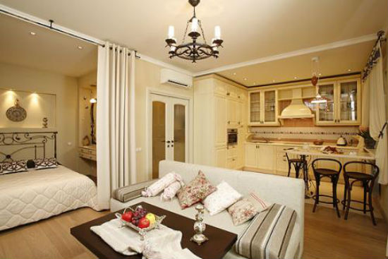 Спальня в квартире-студии с зонированием шторами и диваном