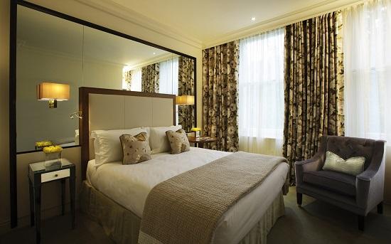 Большое зеркало на стене у кровати в интерьере спальни