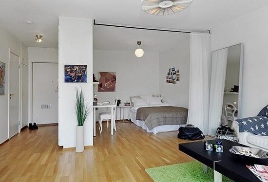 Ограждение спальной зоны в гостиной при помощи занавески на карнизе