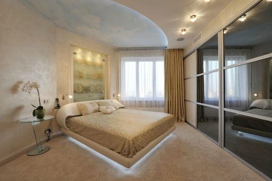 Встроенная гардеробная шкаф-купе со стеклянными створками в спальне