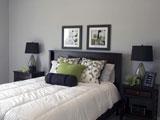 Серые однотонные обои и черная мебель в спальне