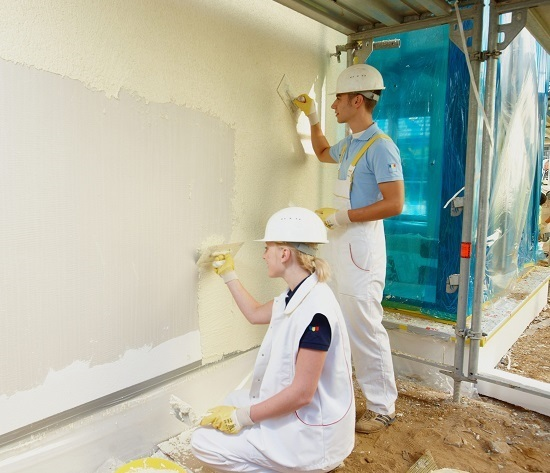 Процесс нанесения штукатурки короед на стену дома