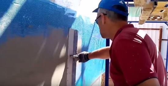 Закрепление и разглаживание сетки перед оштукатуриванием стены