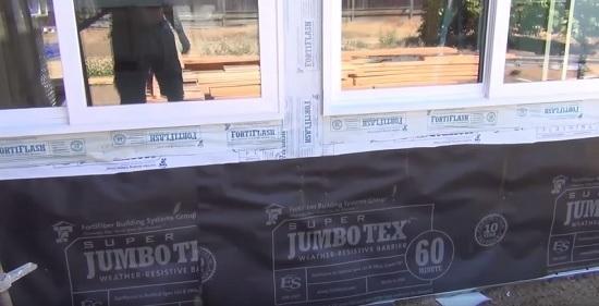 Монтаж слоя строительной бумаги на фасад перед оштукатуриванием