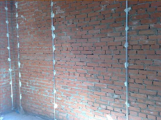 Установленные на кирпичную стену маяки для штукатурки