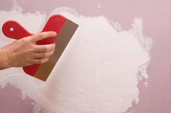 Нанесение широким шпателем финишной штукатурной смеси на стены