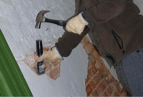 Использование долота для снятия со стены штукатурки