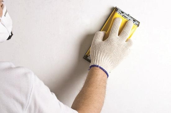 Шлифовка поверхности стены из гипсокартона после штукатурных работ