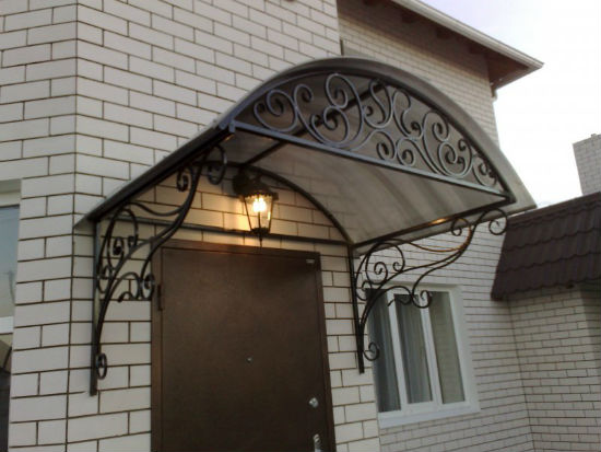 Кованый козырек-навес навесной конструкции с крышей из поликарбоната